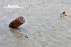 在海滩的空的玻璃瓶 库存照片