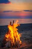 在海滩的篝火由日落的海 图库摄影