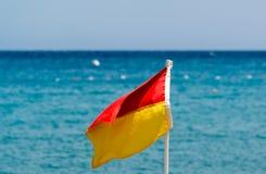 在海滩的红色和黄旗在海的背景 库存照片