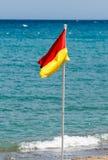 在海滩的红色和黄旗在海的背景 免版税库存图片