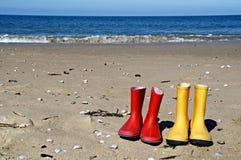 在海滩的红色和黄色雨靴 免版税图库摄影