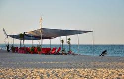 在海滩的红色躺椅 免版税库存图片