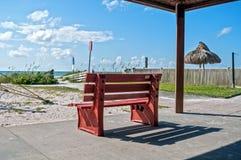 在海滩的红色长凳 免版税库存照片