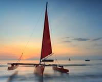在海滩的红色风船与美好的日落 免版税库存照片