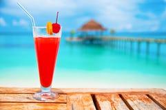 在海滩的红色饮料 库存照片
