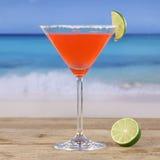 在海滩的红色鸡尾酒马蒂尼鸡尾酒饮料 图库摄影