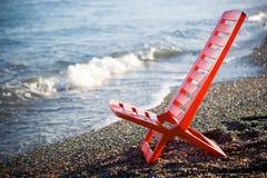 在海滩的红色轻便折叠躺椅 图库摄影