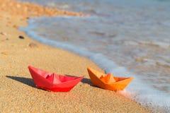 在海滩的纸小船 免版税库存照片