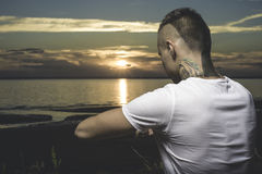 年轻在海滩的纹身花刺人实践的瑜伽 图库摄影