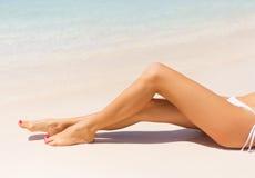 在海滩的美丽的亭亭玉立的妇女的腿 库存图片