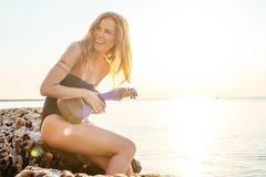 在海滩的美丽的女性使用的尤克里里琴 库存照片