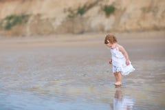 在海滩的美丽的小的女婴佩带的白色礼服 免版税库存照片