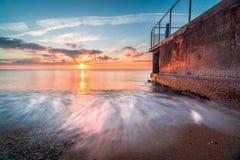 在海滩的美好的剧烈的温暖的日出与清楚的蓝色和橙色天空 图库摄影