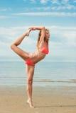 在海滩的美好的女子瑜伽 图库摄影