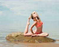 在海滩的美好的女子瑜伽 免版税库存照片