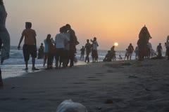在海滩的美好的日出场面与人 库存照片