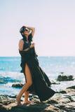 在海滩的美好的时兴的模型在美丽的长的礼服 图库摄影