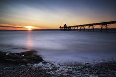 在海洋的美好的长的曝光日落有码头剪影的 免版税库存照片