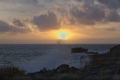 在海滩的美妙的日落 海是风雨如磐的 波浪在岩石打破 库存图片