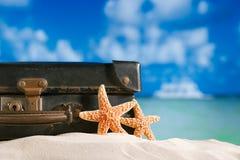 在海滩的老减速火箭的古色古香的手提箱与海星、海洋和天空 库存照片
