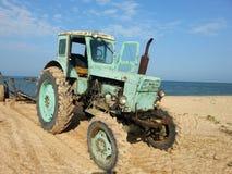 在海滩的老拖拉机 免版税图库摄影