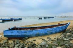 在海滩的老木小船 免版税库存图片