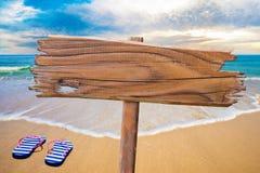 在海滩的老木标志 免版税图库摄影