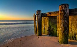 在海滩的老木码头 免版税图库摄影