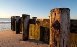 在海滩的老木码头 免版税库存图片