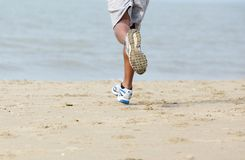 在海滩的背面图公慢跑者 库存照片