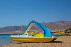 在海滩的脚蹬小船 免版税库存照片