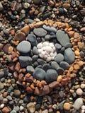 在海滩的色的小卵石圈子 免版税库存图片