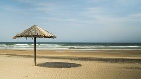 在海滩的茅草屋顶伞 免版税库存照片