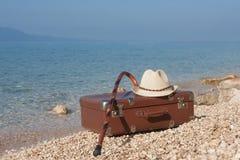 在海滩的葡萄酒皮革手提箱 图库摄影