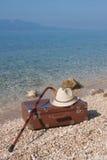 在海滩的葡萄酒皮革手提箱 库存照片