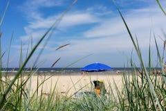 在海滩的蓝色伞在夏天 免版税库存图片