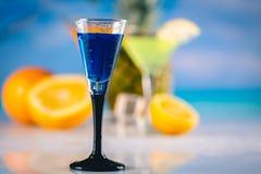 在海滩的蓝色异乎寻常的饮料与棕榈在背景中 免版税图库摄影