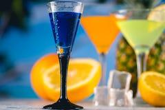 在海滩的蓝色异乎寻常的饮料与棕榈在背景中 免版税库存照片