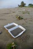 在海滩的被丢掉的外卖纸盒 免版税库存照片