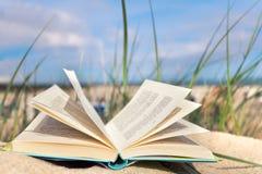 在海滩的被打开的书 库存照片