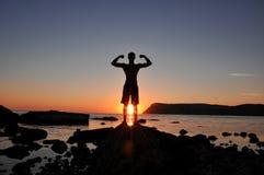 在海滩的训练的男性身体剪影在日落 免版税库存图片