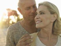 在海滩的资深夫妇消费质量时间 免版税库存照片