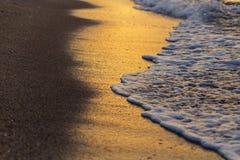 在海滩的软的波浪在创造金黄颜色的日落 免版税库存照片