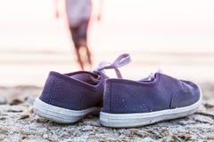 在海滩的运动鞋与连续男孩 库存照片