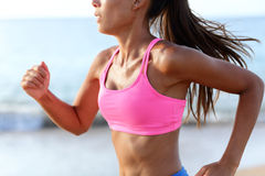 在海滩的连续坚定的冲刺的妇女赛跑者 免版税库存照片