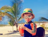 在海滩的逗人喜爱的小男孩饮用的汁液 免版税库存照片