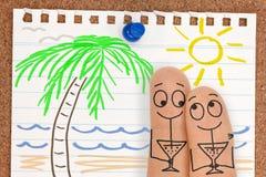 在海滩的逗人喜爱的愉快的手指面孔夫妇与饮料 图库摄影