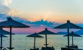 在海滩的遮阳伞在日落 免版税库存图片