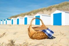 在海滩的野餐与蓝色小屋 免版税库存图片