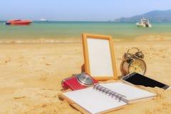 在海滩的金框架与照相机、机动性、笔记本和电话c 免版税库存图片